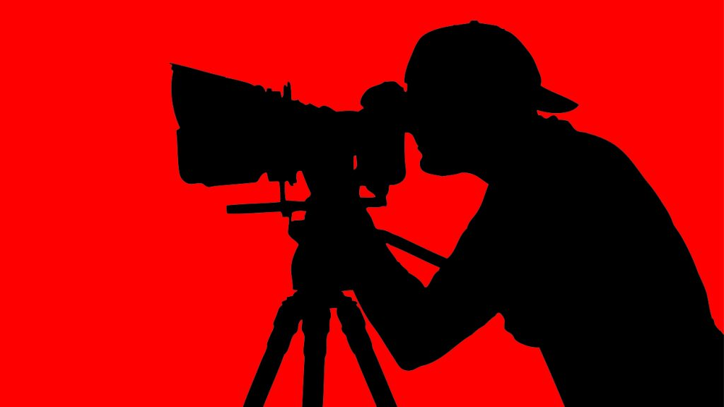 A silhouette of a cameraman looking through the lenses of his camera. He is part of a video production shoot.