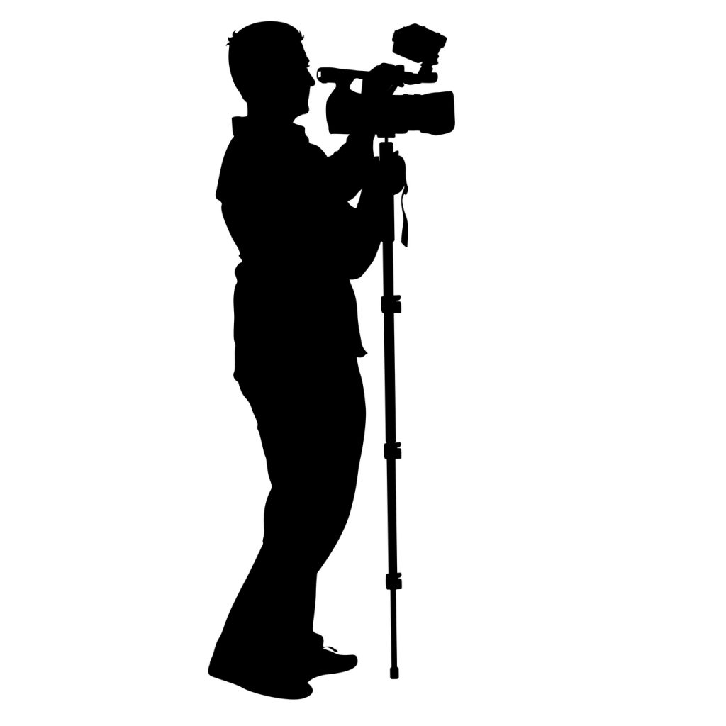 A silhouette of a professional videographer with video camera.