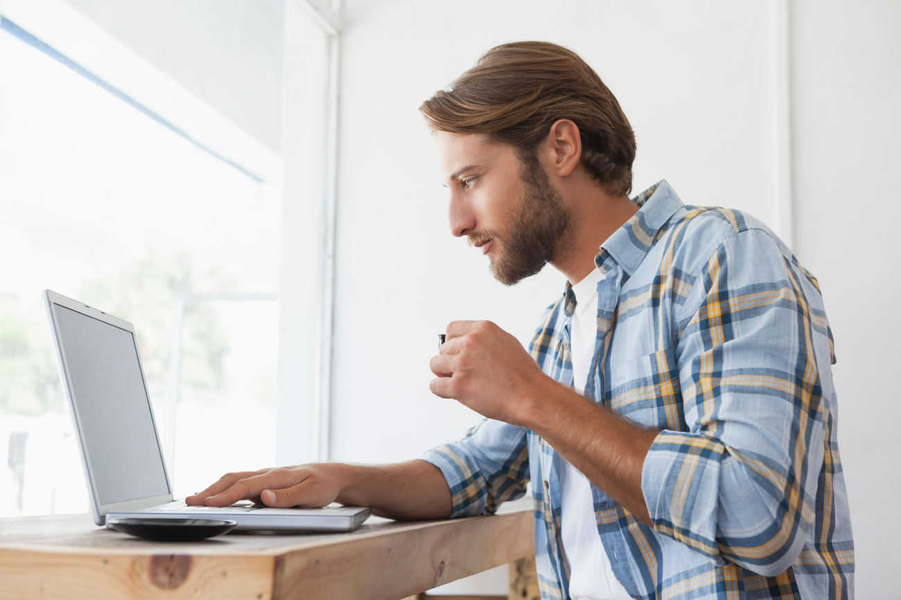A man watching a video on his laptop. He may encounter one of many ad formats while watching his video.