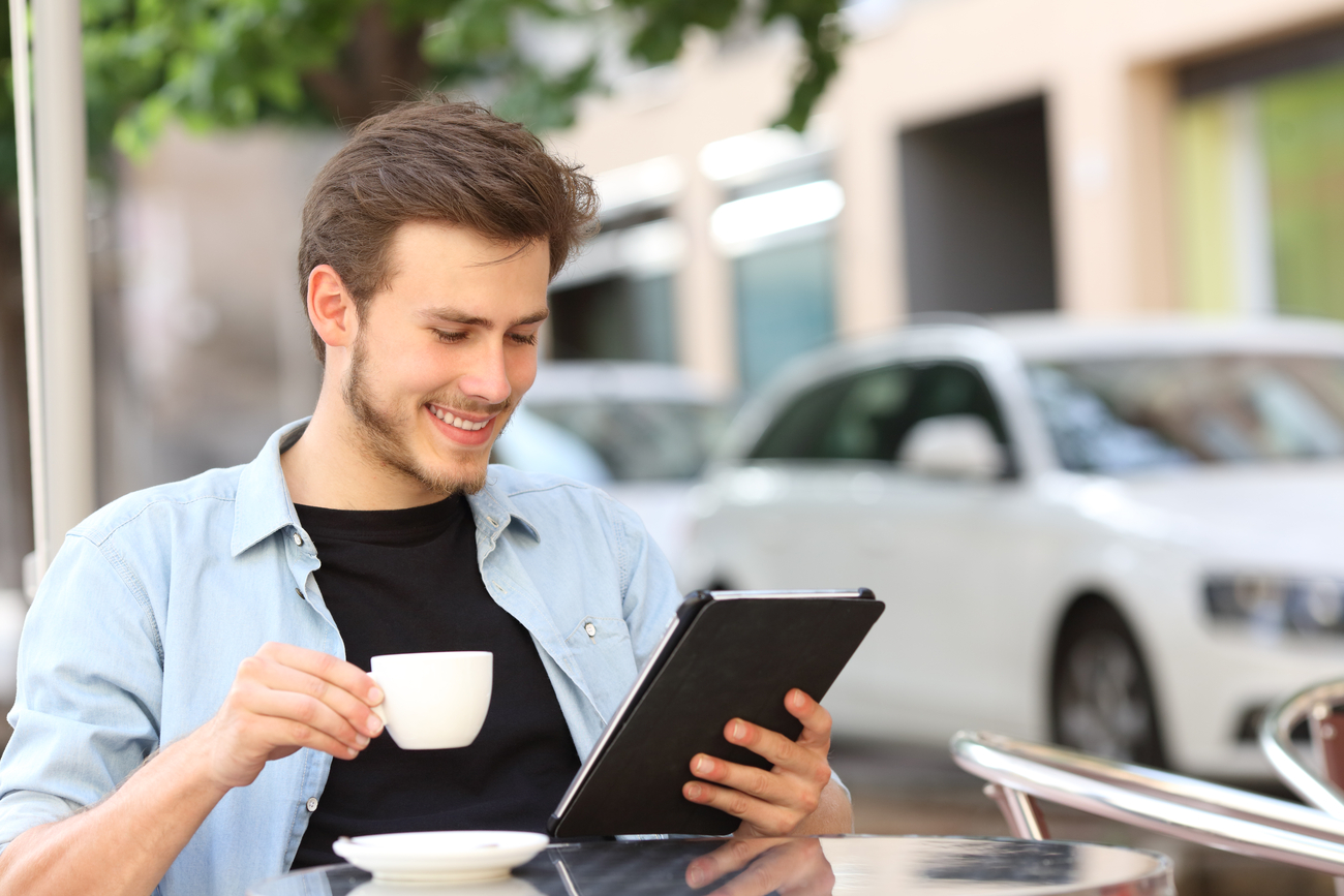 A man is holding his coffee and watching a video on his tablet. He is one of many YouTube subscribers.