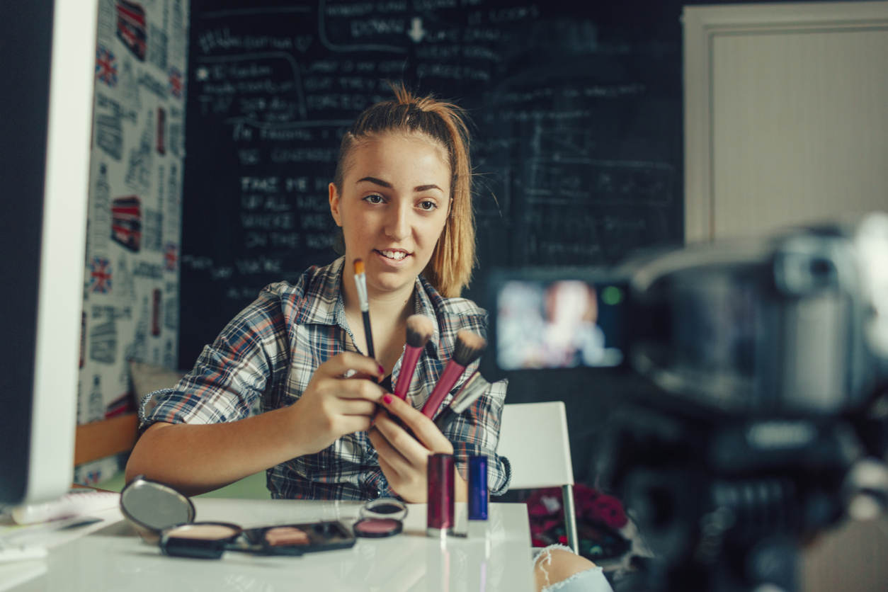 A young makeup vlogger recording a tutorial for her video blog.