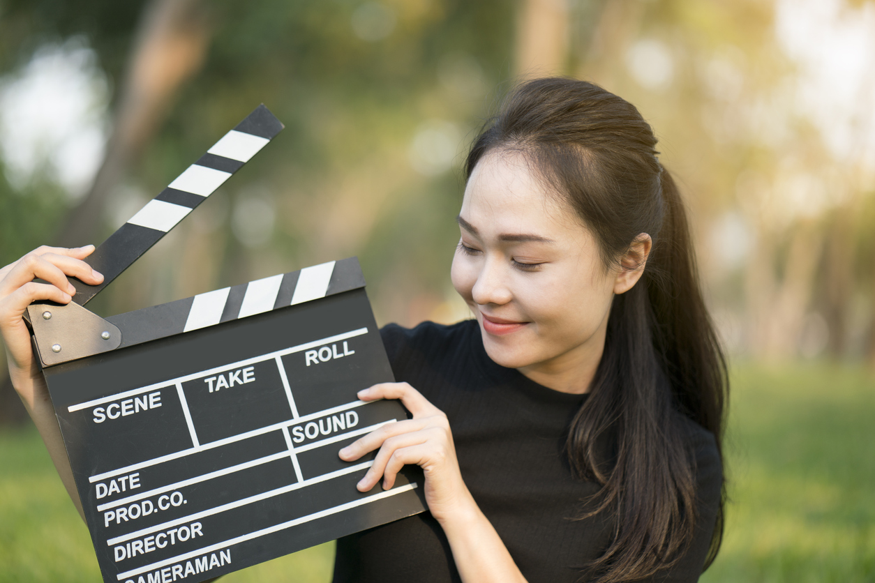 Female line producer holding clapper board in her hands.