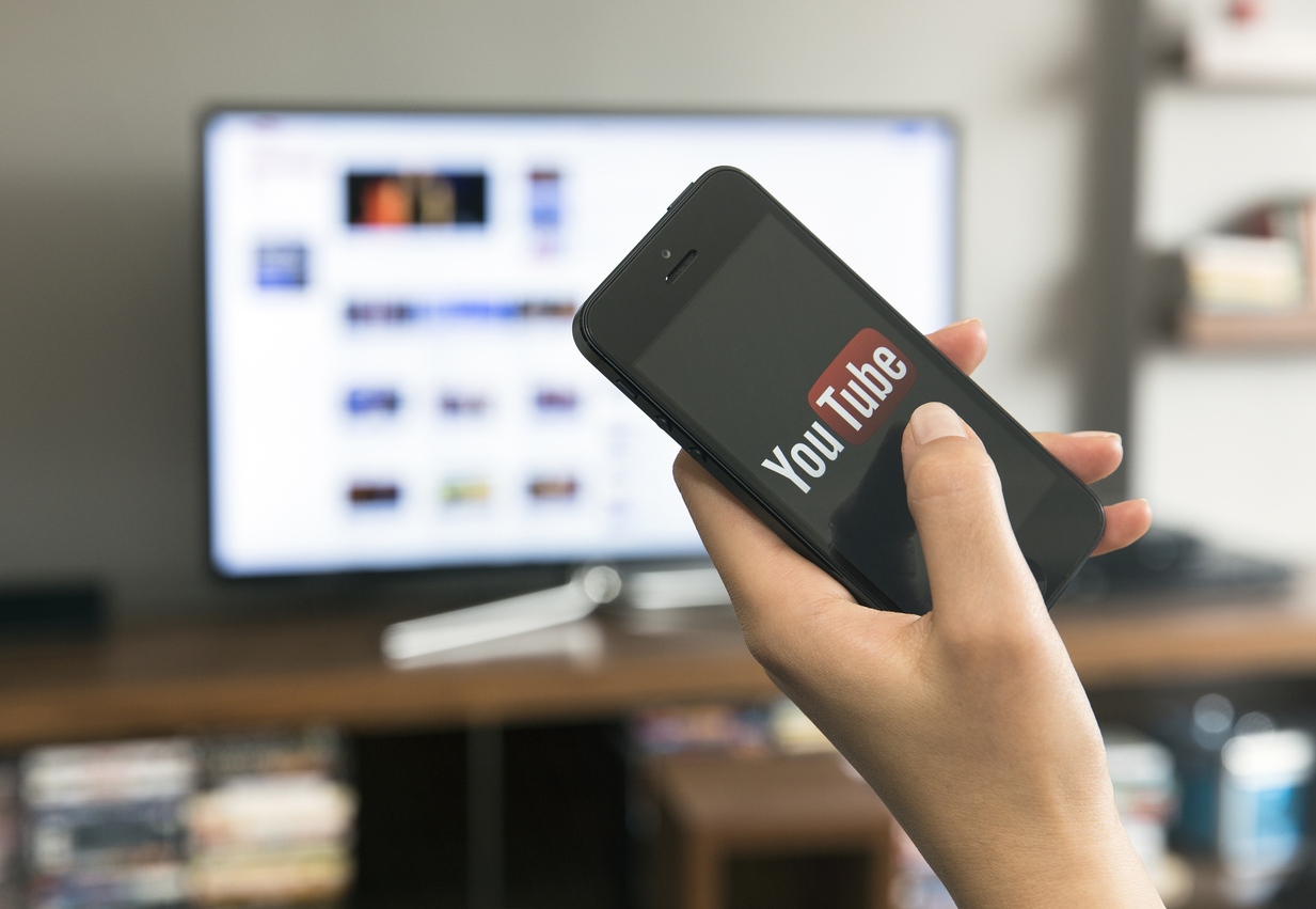 A women with a smartphone in her hand, and in the background is a blurred YouTube Channel on a monitor.