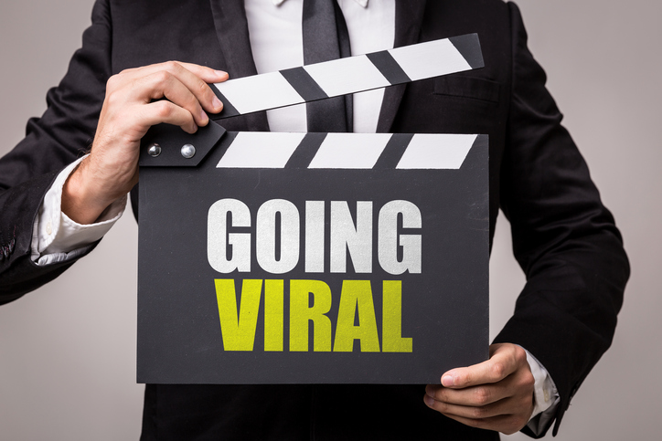 A man in a suit with a sign that says 'Going Viral'
