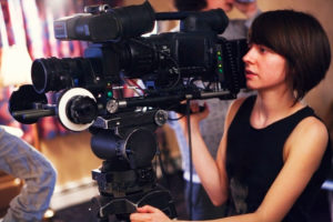 A woman operates a large camera on the set of a premium video production set that costs a premium price tag.